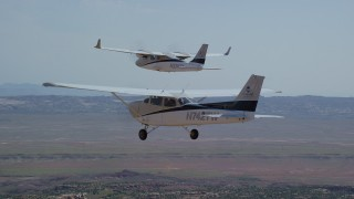 AX139_040 - 6K stock footage aerial video of a Tecnam P2006T and Cessna flying over wide desert, Grand County, Utah