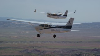 AX139_041 - 6K stock footage aerial video track a Tecnam P2006T and a Cessna flying over desert, Grand County, Utah