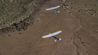 AX139_042 - 6K stock footage aerial video of tracking Tecnam P2006T and Cessna flying over desert, Grand County, Utah