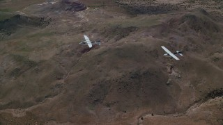 AX139_045 - 6K stock footage aerial video of Tecnam P2006T and Cessna planes flying over desert, Grand County, Utah
