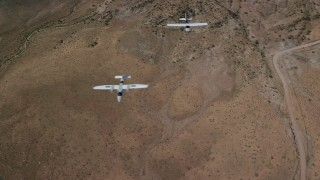 AX139_046 - 6K stock footage aerial video of two planes, Tecnam P2006T and Cessna, flying over desert, Grand County, Utah