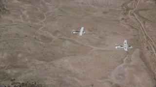AX139_047 - 6K stock footage aerial video of Tecnam P2006T, Cessna flying over desert, Grand County, Utah