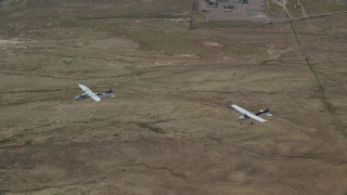 AX139_048 - 6K stock footage aerial video of a pair of airplanes, a Tecnam P2006T and a Cessna, flying over desert, Grand County, Utah