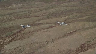 AX139_049 - 6K stock footage aerial video of Tecnam P2006T and Cessna flying above the desert, Grand County, Utah
