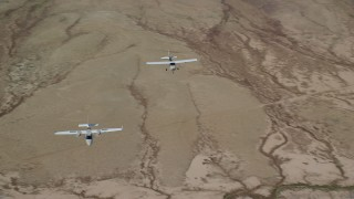 AX139_050 - 6K stock footage aerial video of Tecnam P2006T, Cessna flying over desert, zoom out, Grand County, Utah