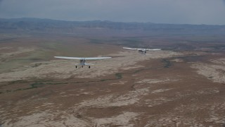 AX139_053 - 6K stock footage aerial video of tracking Tecnam P2006T and Cessna planes flying over desert, Grand County, Utah