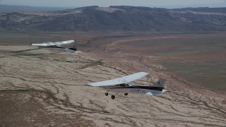 AX139_054 - 6K stock footage aerial video of flying beside Tecnam P2006T and Cessna flying over desert, Grand County, Utah
