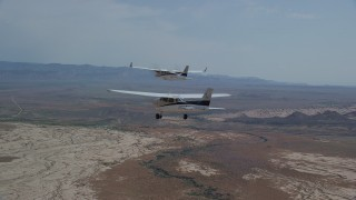 AX139_056 - 6K stock footage aerial video of following Tecnam P2006T and Cessna flying over desert, Grand County, Utah