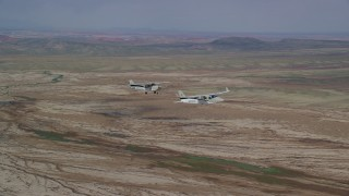 AX139_058 - 6K stock footage aerial video of flying beside a Tecnam P2006T and Cessna flying over desert, Grand County, Utah