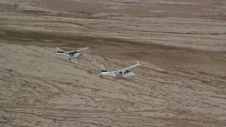 AX139_059 - 6K stock footage aerial video of focusing on Tecnam P2006T and Cessna flying over desert, Grand County, Utah