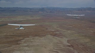 AX139_060 - 6K stock footage aerial video of flying around Tecnam P2006T, Cessna flying over desert, Grand County, Utah