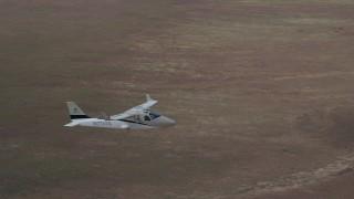 AX139_067 - 6K stock footage aerial video of tracking Tecnam P2006T flying over desert, revealing Cessna, Grand County, Utah