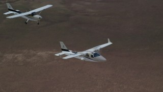 AX139_068 - 6K stock footage aerial video of tracking Tecnam P2006T and Cessna aircraft flying over desert, Grand County, Utah