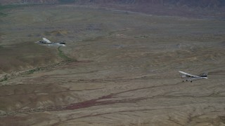 AX139_073 - 6K stock footage aerial video of tracking Tecnam P2006T and Cessna aircraft flying over desert, Grand County, Utah
