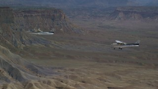 AX139_075 - 6K stock footage aerial video focus on Tecnam P2006T and Cessna flying over desert, Grand County, Utah