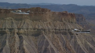 AX139_076 - 6K stock footage aerial video of Tecnam P2006T and Cessna flying past mesas, Grand County, Utah
