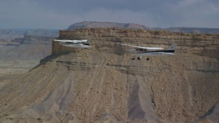 AX139_077 - 6K stock footage aerial video of tracking Tecnam P2006T and Cessna flying by desert mesas, Grand County, Utah