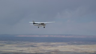 AX139_081 - 6K stock footage aerial video of a Cessna airplane flying over desert, Grand County, Utah
