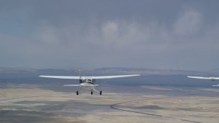 AX139_082 - 6K stock footage aerial video tracking Cessna airplane over desert, revealing Tecnam P2006T, Grand County, Utah