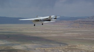 AX139_083 - 6K stock footage aerial video track Tecnam P2006T and Cessna flying over desert, Grand County, Utah