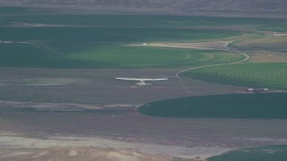 AX139_087 - 6K stock footage aerial video of tracking Tecnam P2006T near circular crop fields, reveal Cessna, Green River, Utah