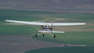 AX139_088 - 6K stock footage aerial video of a Tecnam P2006T near circular crop fields, reveal Cessna, Green River, Utah