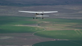 AX139_089 - 6K stock footage aerial video of tracking Cessna and Tecnam P2006T over circular crop fields, Green River, Utah