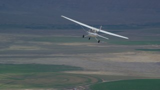 AX139_090 - 6K stock footage aerial video tracking Cessna airplane over circular crop fields, Green River, Utah