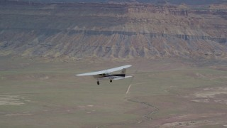 AX139_091 - 6K stock footage aerial video of an air to air view of a Cessna flying over desert, Green River, Utah