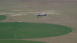 AX139_092 - 6K aerial stock footage video of a Cessna airplane over circular crop field, Green River, Utah
