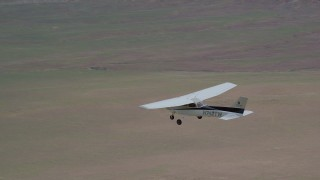 AX139_094 - 6K stock footage aerial video of an air to air view of a Cessna over desert and circular crop fields, Green River, Utah