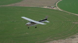 AX139_097 - 6K stock footage aerial video of an air to air view of a Cessna over circular crop fields, Green River, Utah