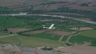 AX139_098 - 6K stock footage aerial video of tracking Cessna over farmland and desert hills, Green River, Utah
