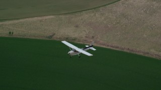 AX139_100 - 6K stock footage aerial video track a Cessna over circular crop fields from above, Green River, Utah