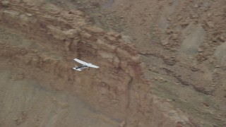 AX139_102 - Aerial stock footage of Tracking Cessna flying by desert buttes, Emery County, Utah