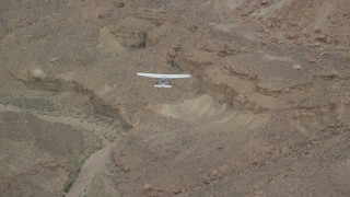 AX139_103 - Aerial stock footage of Tracking Cessna flying by desert cliffs, Emery County, Utah