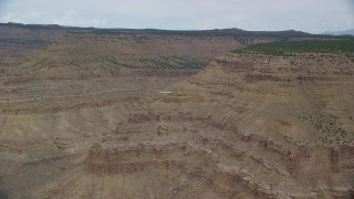 AX139_104 - Aerial stock footage of Tracking Cessna flying by desert mesas, Emery County, Utah
