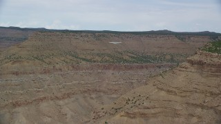 AX139_105 - Aerial stock footage of Tracking Cessna flying by desert mesas, Emery County, Utah
