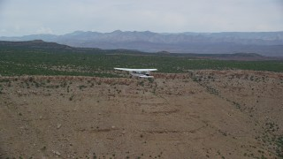 AX139_107 - Aerial stock footage of Tracking Cessna flying by desert mesas, Emery County, Utah