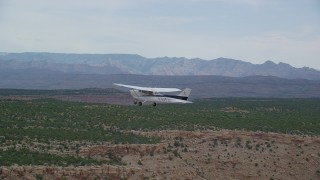 AX139_108 - Aerial stock footage of Tracking Cessna flying by desert mesas, Emery County, Utah
