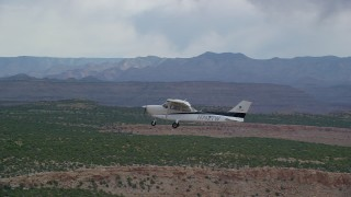 AX139_109 - Aerial stock footage of Tracking Cessna flying by desert mesas, Emery County, Utah