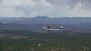 AX139_111 - Aerial stock footage of Tracking Cessna flying by desert mesas, Emery County, Utah