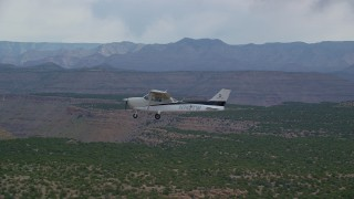 AX139_112 - Aerial stock footage of Tracking Cessna flying by desert mesas, Emery County, Utah