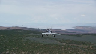 AX139_113 - Aerial stock footage of Tracking Cessna flying by desert mesas, Emery County, Utah