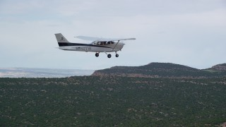 AX139_115 - Aerial stock footage of Tracking Cessna flying over desert mesas, Emery County, Utah