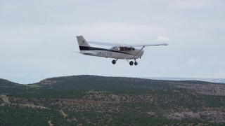 AX139_116 - Aerial stock footage of Tracking Cessna flying over desert mesa, drop out of frame, Emery County, Utah
