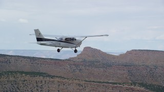 AX139_117 - Aerial stock footage of Revealing and tracking Cessna over desert, Emery County, Utah