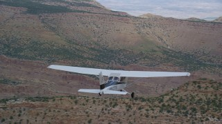 AX139_118 - Aerial stock footage of Tracking Cessna flying over desert, near wide canyon, Emery County, Utah