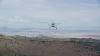 AX139_120 - Aerial stock footage of Tracking Cessna over desert near ridge, ascend out of frame, Emery County, Utah