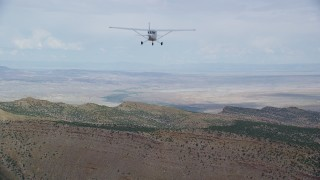 AX139_121 - Aerial stock footage of Approaching mountain ridge, Cessna descends into frame, Emery County, Utah